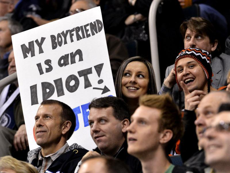 A Winnipeg Jets fan holds a sign next to her boyfriend wearing a Philadelphia Flyers hat during the second period of their NHL hockey game in Winnipeg. Reuters