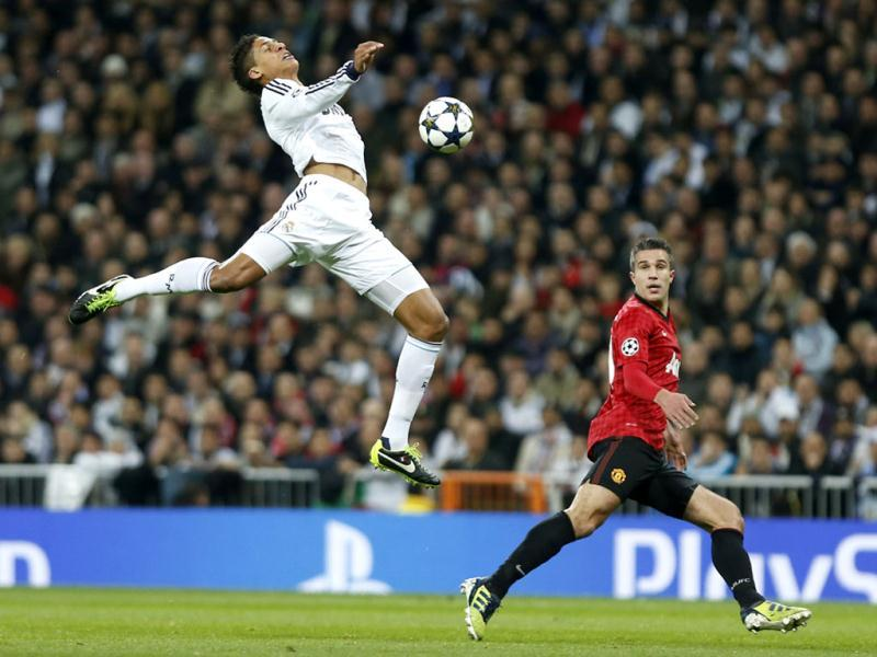 Manchester United's Robin van Persie watches as Real Madrid's Raphael Varane from France tries to intercept the ball during the Champions League match between Real Madrid and Manchester United at the Santiago Bernabeu stadium in Madrid. AP Photo