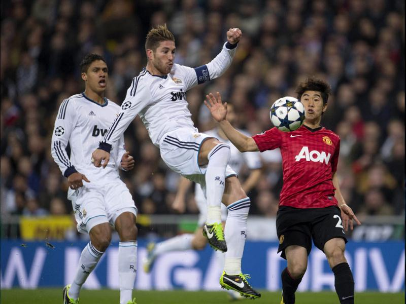 Real Madrid's defender Sergio Ramos (C) vies with Manchester United's Japanese midfielder Shinji Kagawa (R) during the UEFA Champions League match between Real Madrid and Manchester United at the Santiago Bernabeu stadium in Madrid. AFP