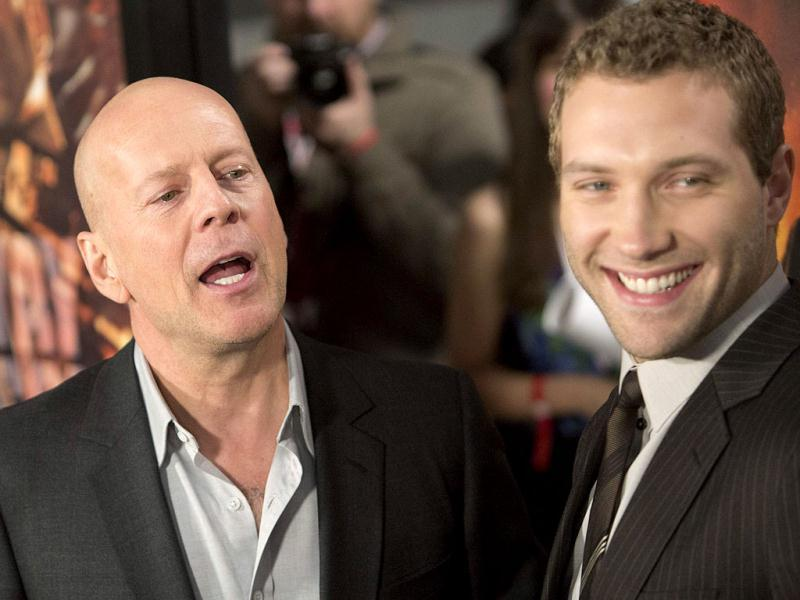 Cast members Jai Courtney (R) and Bruce Willis meet with fans to celebrate the opening of their new film