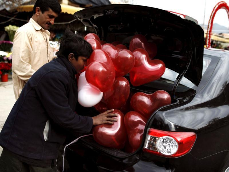 A man tries to fit heart-shaped balloons in the trunk of his car on Valentine's Day in Islamabad. Reuters Photo
