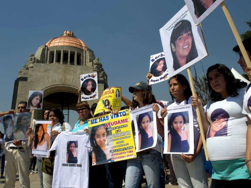 People show pictures of missing women during Mexico's