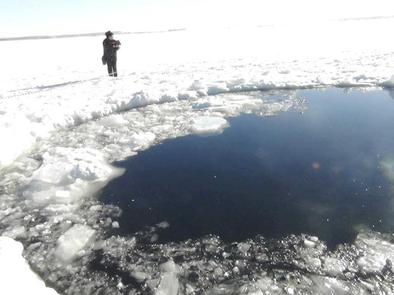 A Russian policeman works near an ice hole, which is said to be the point of impact of a meteorite seen earlier in the Urals region, at lake Chebarkul some 80 kilometers (50 miles) west of Chelyabinsk as per the Interior Ministry department for Chelyabinsk. (Reuters)