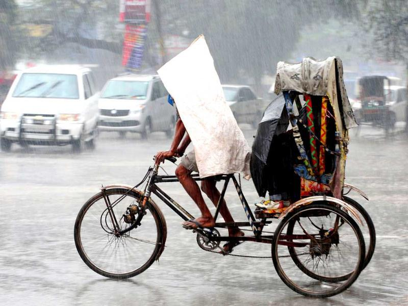 A rickshaw puller wears a tarp as he cycles customers during heavy rain in Allahabad. AFP