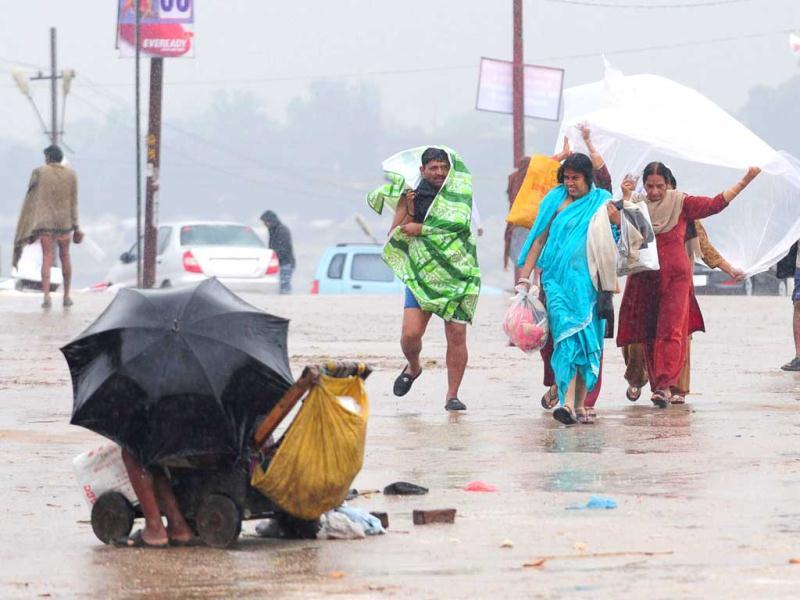 Devotees cover themselves with plastic sheets during heavy rain at Sangam in Allahabad. AFP