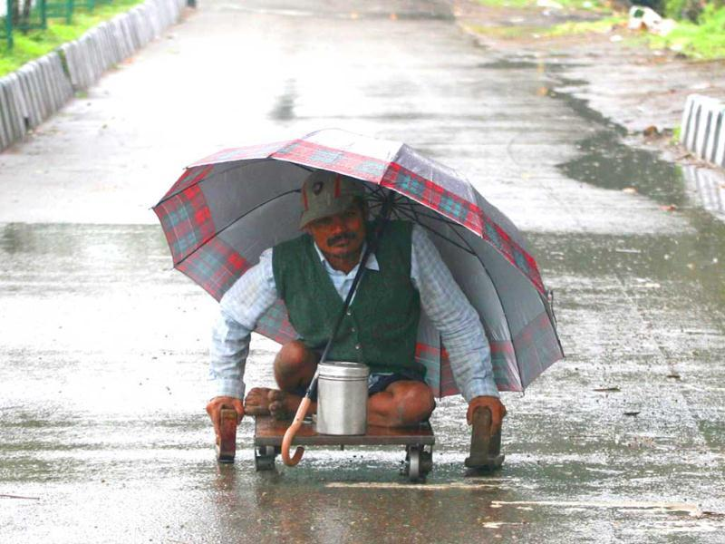 A beggar goes about his work despite the rain shielded by an umbrella in Jammu. UNI