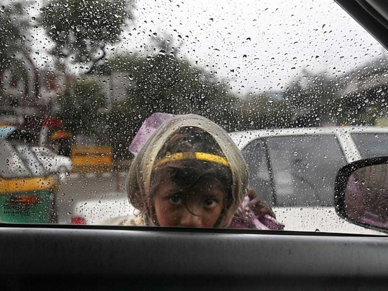 An infant looking through car glass window with misty eyes as it rains with overcast sky, near India Gate, in New Delhi. Raj K Raj/HT Photo