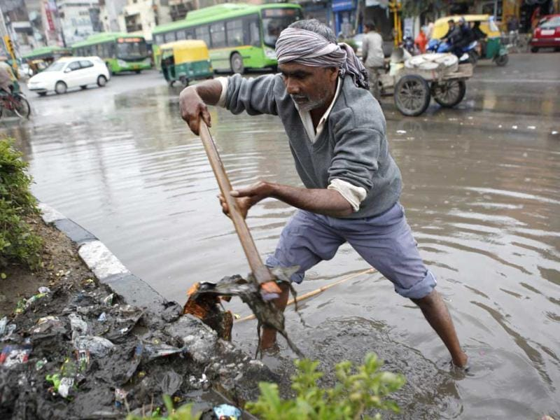 A MCD worker clears a waterlog as it rains with overcast sky in New Delhi. Raj K Raj/HT Photo