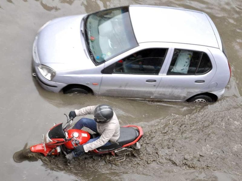 Vehicles caught in the rain on a waterlogged road near NHPC Chowk after heavy rain in Faridabad. UNI