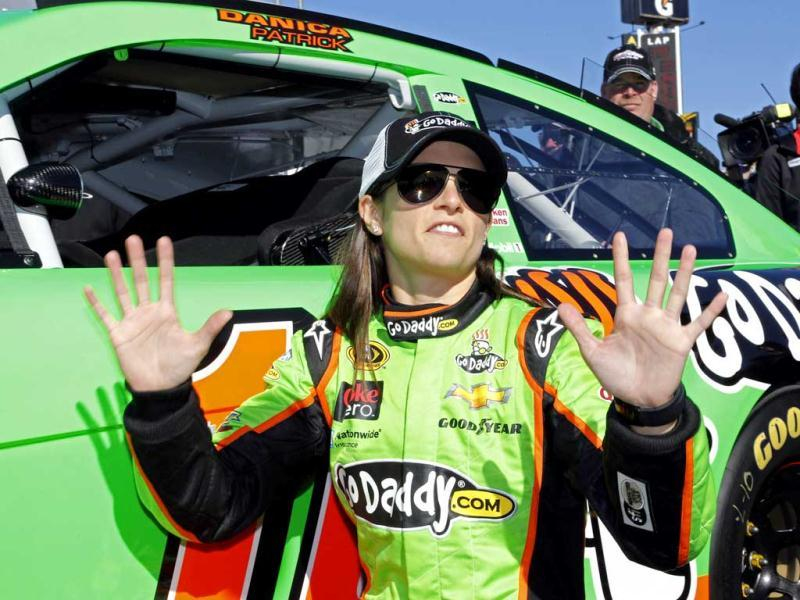 Danica Patrick gestures to photographers as she poses by he car after winning the pole during qualifying for the NASCAR Daytona 500 Sprint Cup Series auto race at Daytona International Speedway, in Daytona Beach, Fla. (AP Photo)