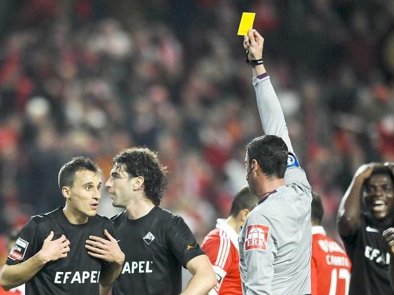Academica's defender Joao Dias (L) receives a yellow card from the referee Nuno Almeida (2nd R) during a Portuguese League football match at Luz Stadium in Lisbon. (AFP Photo)