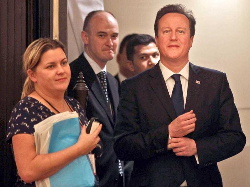 British Prime Minister David Cameron, center, arrives to deliver a speech at a business seminar in Mumbai. AP