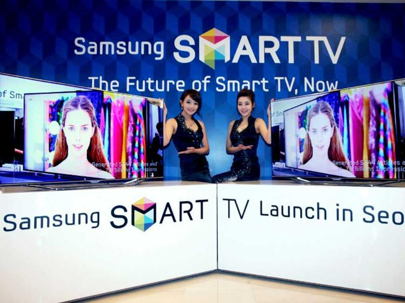 A handout photo released by Samsung Electronics shows South Korean models posing with Samsung Electronics new smart TV, named ES8000, during its launching event in Seoul. Photo: AFP / HO / Samsung Electronics