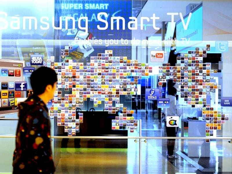 A South Korean man walks past a Samsung smart TV advertisement at a showroom in Seoul on January 28, 2011. Samsung Electronics said fourth-quarter net profit 3.42 trillion won ($3.07 billion), but forecast a challenging few months ahead after a record-setting year. Photo: AFP / Park Ji-Hwan