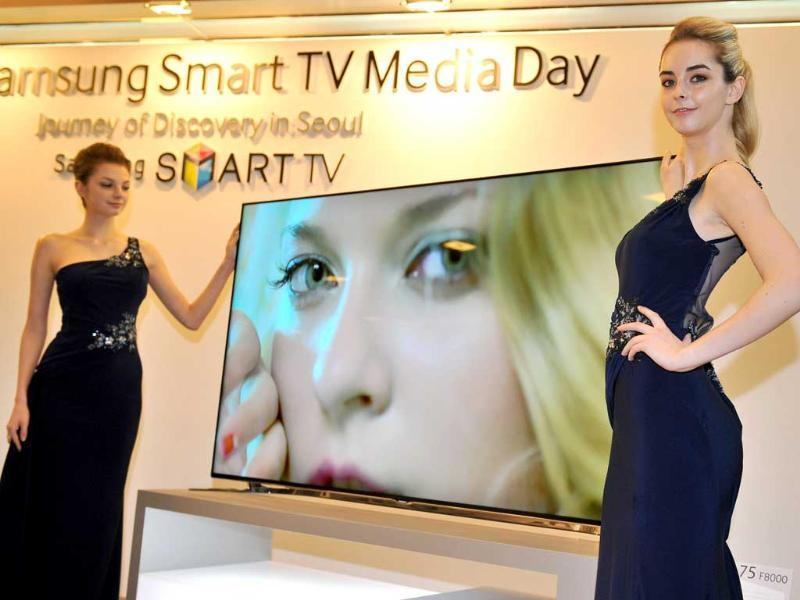 Models pose with Samsung Electronics' new 75 inch F8000 Smart LED TV during a media conference in Seoul on February 19, 2013. South Korea's Samsung Electronics on February 19 launched a set of giant, Internet-enabled televisions aimed at boosting profit margins and cementing its lead on the world's TV markets hit by slowing global demand. Photo: AFP / Jung Yeon-Je
