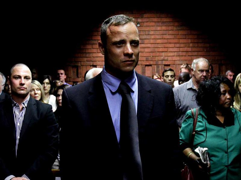 Oscar Pistorius awaits the start of court proceedings while his brother Carl (L) looks on, in the Pretoria Magistrates court. Reuters