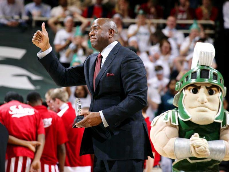 Magic Johnson acknowledges fans as he is honored during a timeout in an NCAA college basketball game between Michigan State and Indiana in East Lansing. (AP)