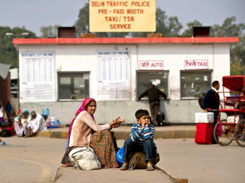 A woman and her son wait outside a pre-paid auto-rickshaw and taxi booth at the New Delhi Railway Station. Millions of workers walked off their jobs in a two-day nationwide strike called by trade unions to protest at the