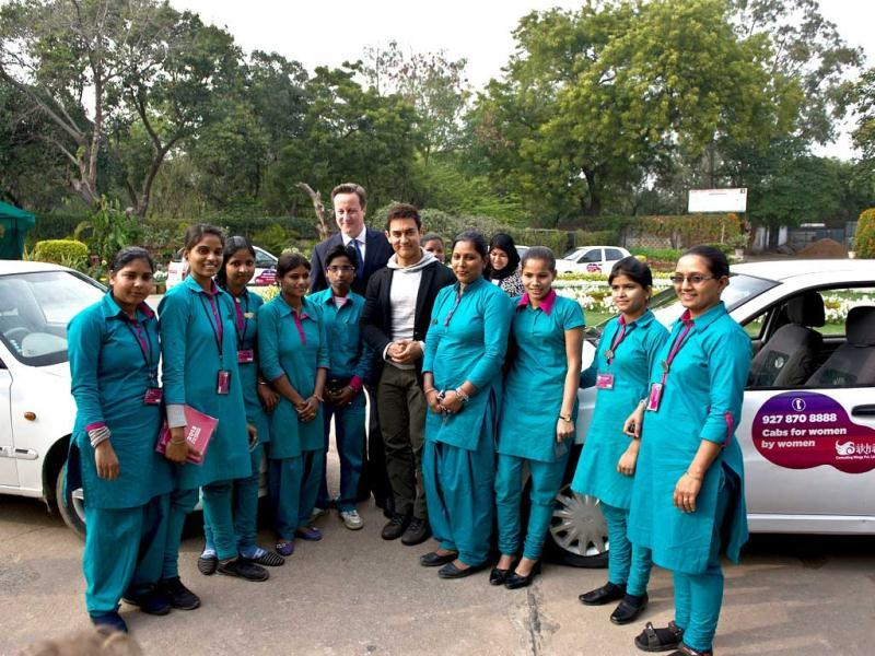 British Prime Minister David Cameron, center left, and Aamir Khan, center right, pose with Indian women cab drivers from Sakha cab services at the Janki Devi Memorial College. (AP Photo)