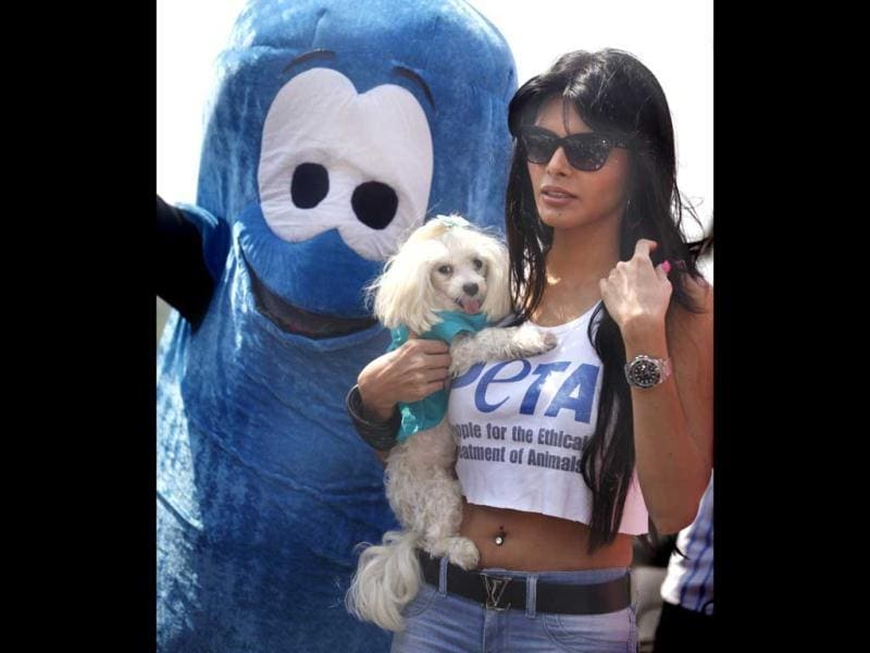 Sherlyn Chopra holds her pet poodle as she leaves after attending an awareness campaign by PETA in Mumbai on Tuesday. (HT Photo)