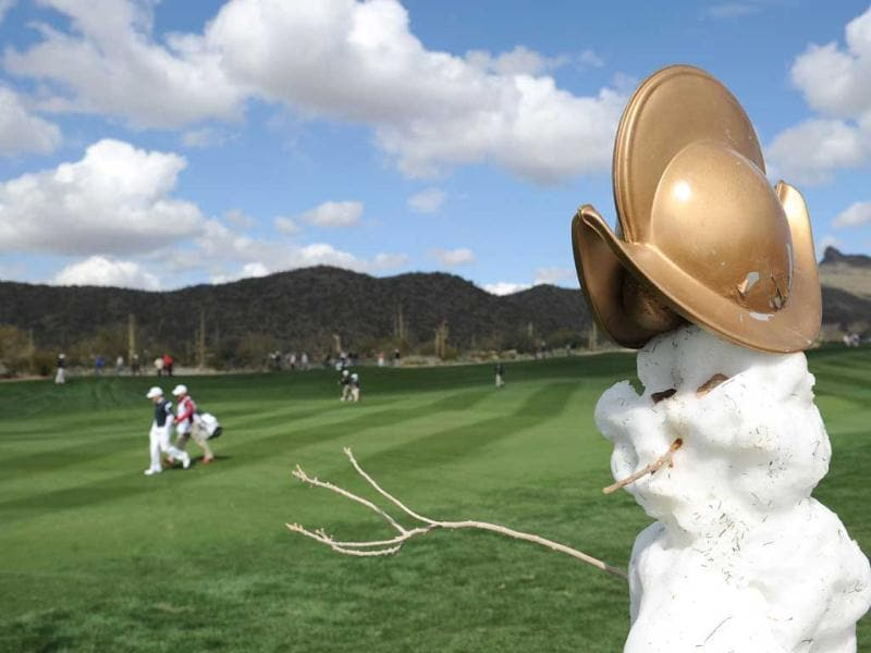 Players walk past a snow man on the second hole during the first round of the World Golf Championships - Accenture Match Play at the Golf Club at Dove Mountain in Marana, Arizona. (AFP)