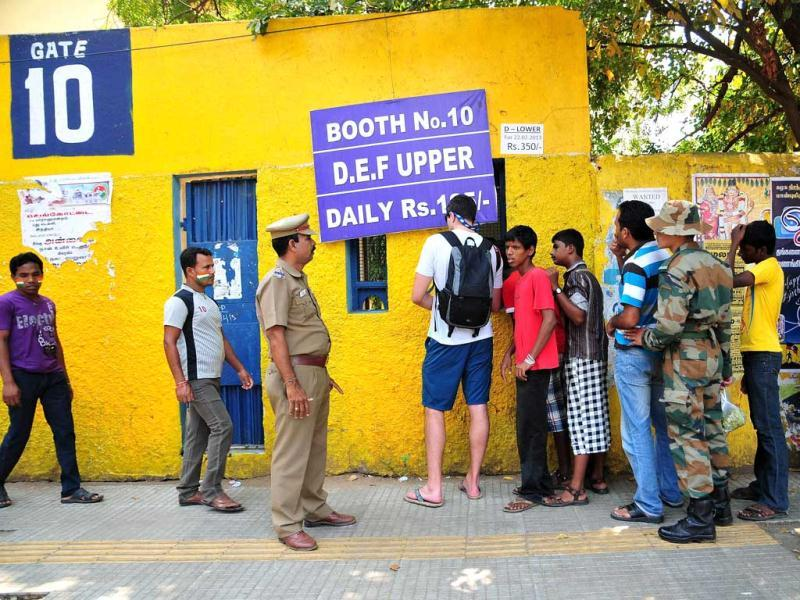 Fans line up to buy tickets for the cricket match between Australia and India as police look on in Chennai. AFP Photo