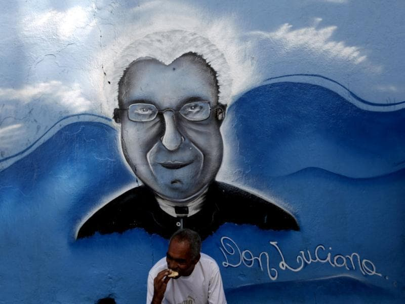 A homeless man eats a biscuit in front of a graffiti of Priest Luciano at the Sao Martinho de Lima Community Center, under the Guadalajara viaduct in the Mooca neighborhood of Sao Paulo. The community center was built in honor of Priest Luciano, who helped many homeless in the region. REUTERS