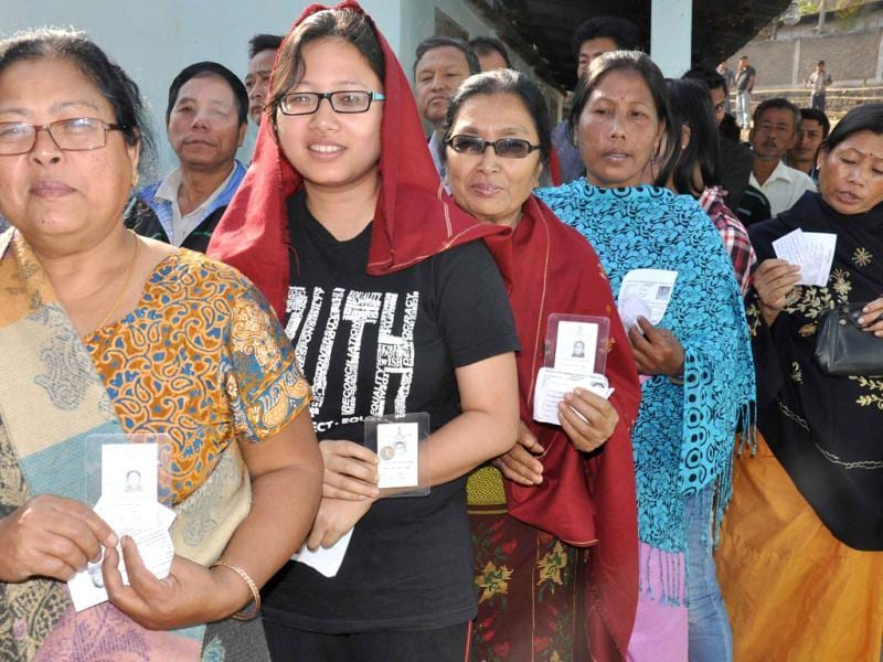 Women show their voter ID cards as they queue up to cast their vote at Pillangkata centre in Meghalaya. UNI