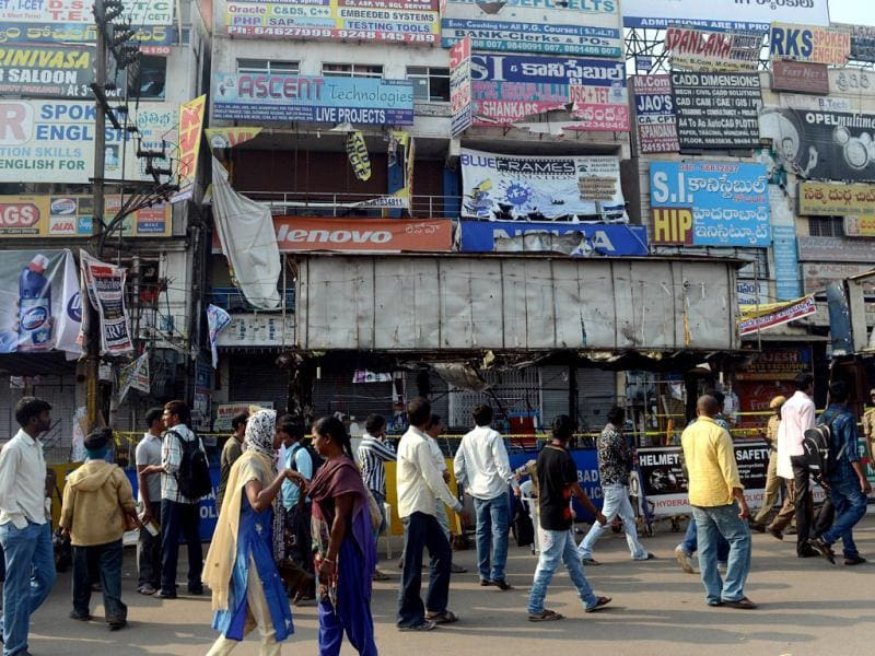 Policemen and pedestrians look on at the site of the bomb blast at Dilsukhnagar in Hyderabad. AFP/Indranil Mukherjee