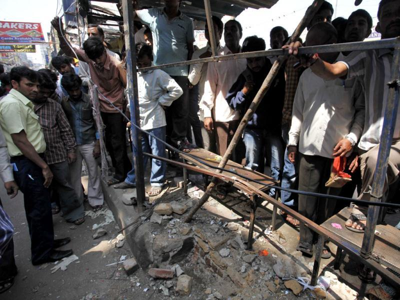 People gather at one of the two bomb blast sites in Hyderabad. The surveillance camera installed in front of Dilsukhnagar bus station captured the image of a suspect. AP/Mahesh Kumar A