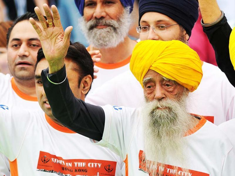 Indian-born British national Fauja Singh, 101 (R) waves to the media after crossing the finish line in the 10-km event as part of the Hong Kong Marathon. Singh retired from competitive races after the marathon. AFP photo