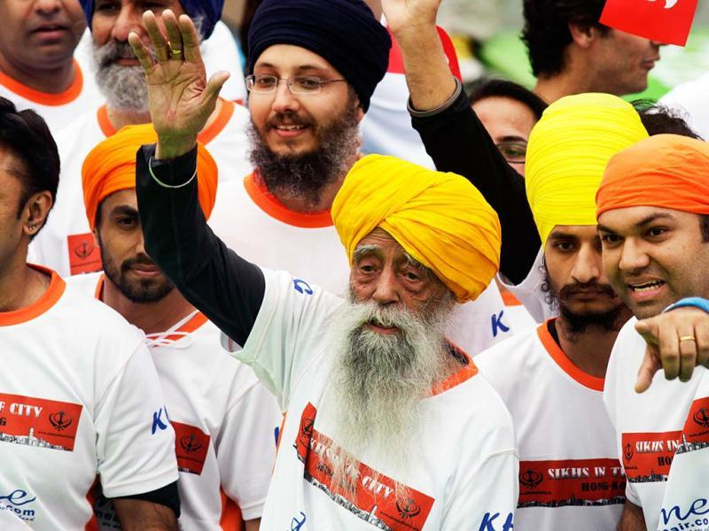 British Indian marathon runner Fauja Singh, 101, and accompanied by othet runners wave to fans after finishing the 10-kilometer race of the Hong Kong Marathon. Singh retired from competitive races after the marathon. Reuters photo