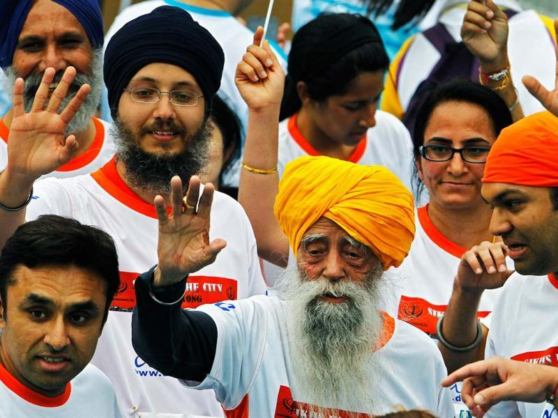 Marathon runner Fauja Singh, 101, center, originally from Beas Pind, in Jalandhar, now living in London, waves after finishing a 10-kilometer race, which was part of the annual Hong Kong Marathon. AP photo