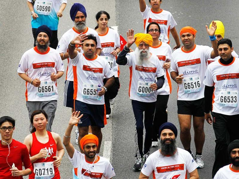 Marathon runner Fauja Singh, 101, center, originally from Beas Pind, in Jalandhar, now living in London, runs in a 10-kilometer race, part of the annual Hong Kong Marathon. AP photo