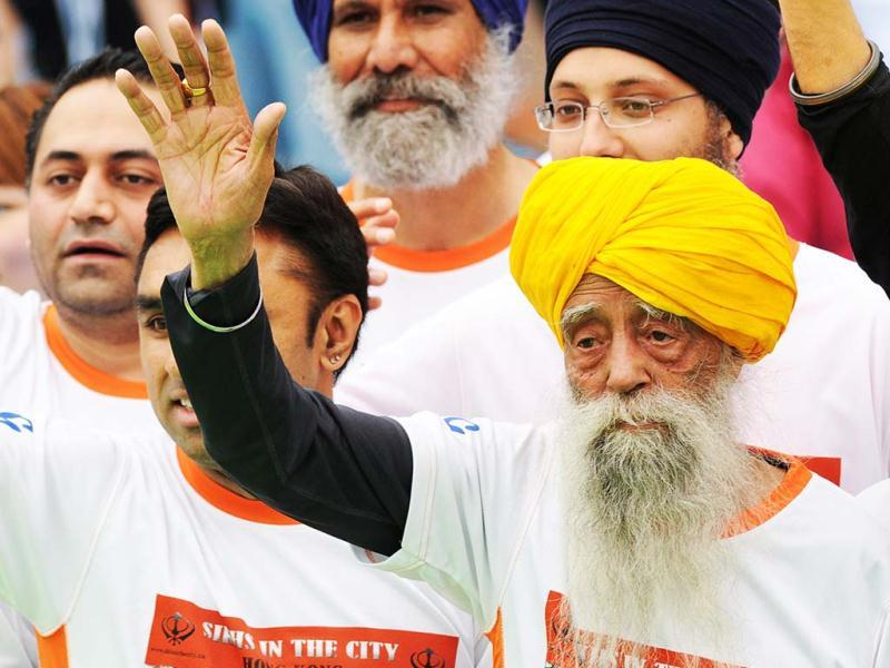 Fauja Singh waves to the media after crossing the finish line in the 10-km event as part of the Hong Kong Marathon. (AFP)