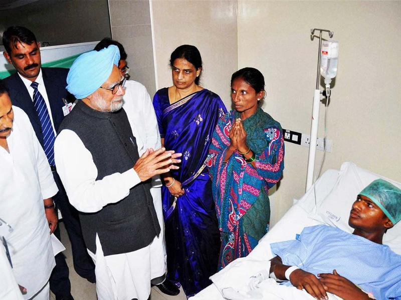 Prime Minister Manmohan Singh and chief minister of Andhra Pradesh N Kiran Kumar Reddy interact with a victim of the Hyderabad bomb blasts. PTI