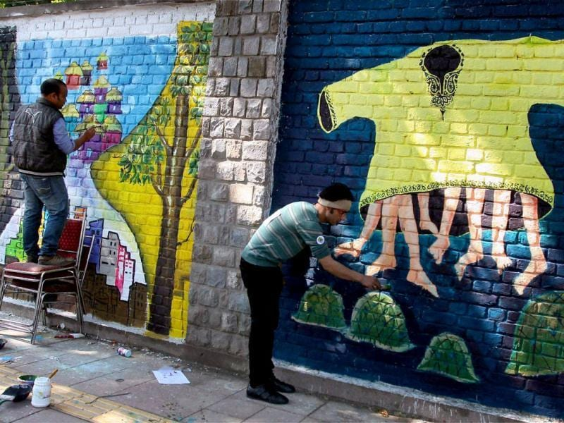 Artists create wall paintings during the 'Design The Change' wall art event in New Delhi. The activity brought together more than 500 professional and budding artists on the same platform to create the wall art.PTI