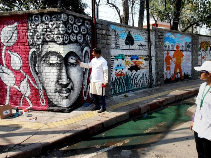 Artists create wall paintings during the 'Design The Change' wall art event in New Delhi. The activity brought together more than 500 professional and budding artists on the same platform to create the wall art. PTI