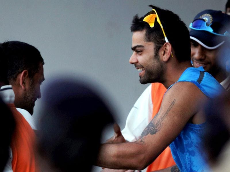 Virat Kohli greets MS Dhoni in the dressing room on the third day of the first Test match against Australia at MA Chidambaram stadium in Chennai. (PTI Photo)