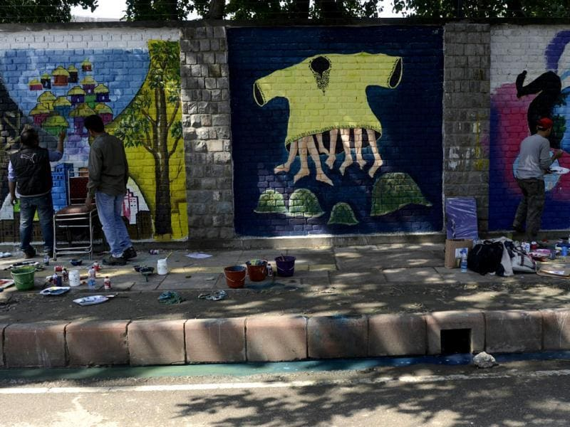 An artist walk past wall paintings created during the 'Design The Change' wall art event in New Delhi. The activity brought together more than 500 professional and budding artists on the same platform to create the wall art. AFP