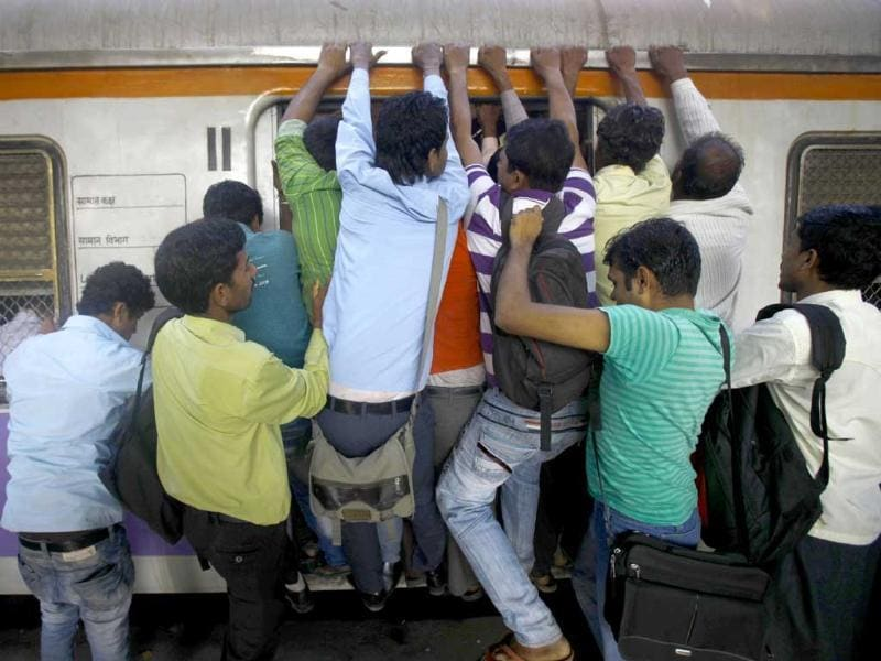 Commuters try to board an overcrowded train in Mumbai. Railway minister Pawan Kumar Bansal presented the rail budget for next fiscal year in the parliament. AP Photo