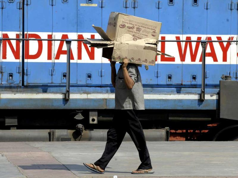 A passenger carries a carton box on his head at a railway station in Hyderabad. AFP PHOTO
