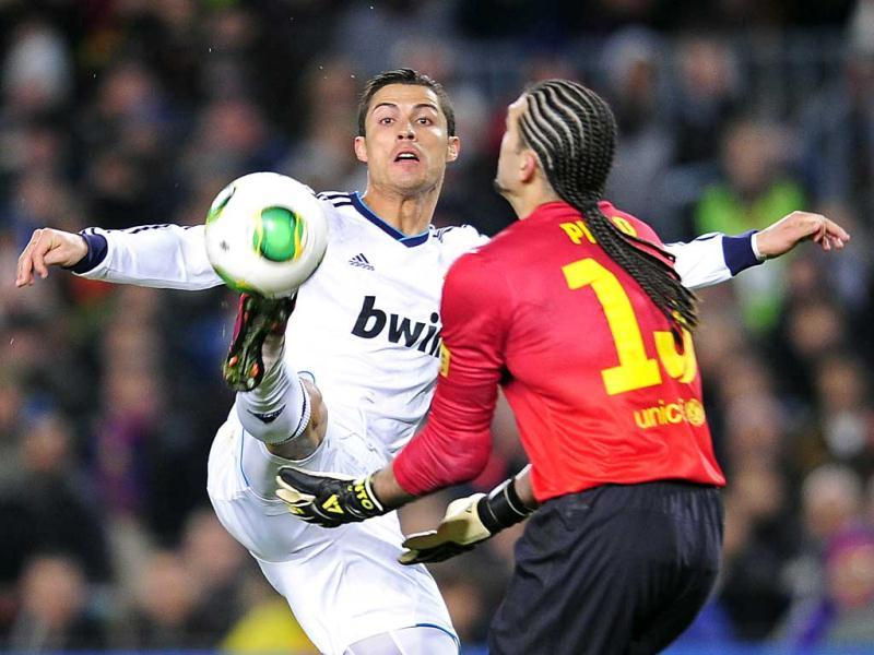 Real Madrid's Cristiano Ronaldo, left, from Portugal, and Barcelona's goalkeeper Jose Manuel Pinto challenge for the ball during a Copa del Rey match at the Camp Nou stadium in Barcelona, Spain. AP Photo