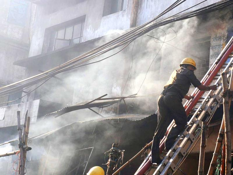 Firefighters climb a ladder as they attempt to control a blaze in the Surya Sen market building in Kolkata. AFP photo
