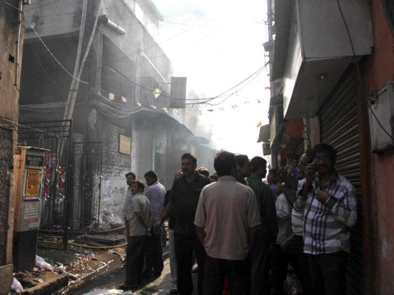 Residents and onlookers wait outside the buildings where a fire broke out at an illegal six-story plastics market in Kolkata. AP photo