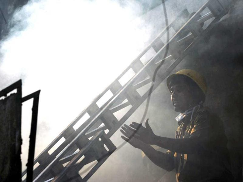 A firefighter gestures as he attempts to control a blaze in the Surya Sen market building in Kolkata. AFP photo