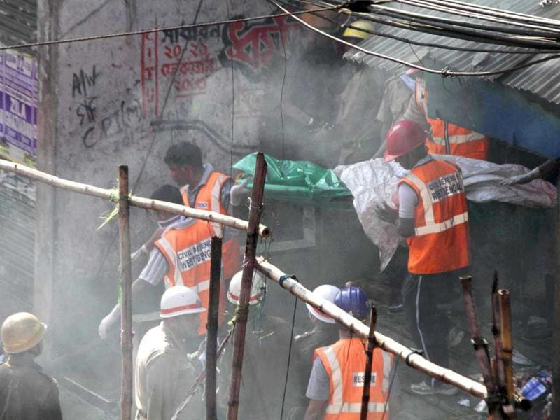 Rescue workers carry a victim's body wrapped in plastic bag after a fire broke out early morning at an illegal six-story plastics market in Kolkata. AP photo