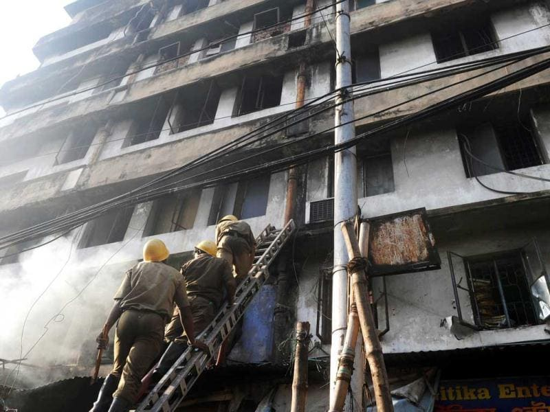 Firefighters climb a ladder to reach to the second floor during a blaze in the Surya Sen market building in Kolkata. AFP photo