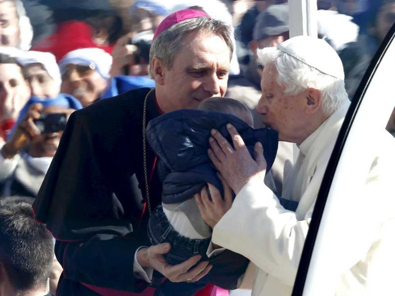 Pope Benedict XVI kisses a baby, held by his personal secretary Georg Gaenswein, as he arrives in St Peter's Square. He said he had great trust in the Church's future and asked for prayers for cardinals choosing his successor at a time of crisis. Reuters/Alessandro Bianchi