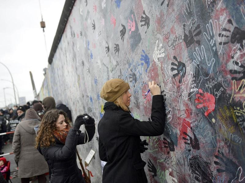 A woman writes on a part of the East Side Gallery, a 1.3 km long remainder of the Berlin Wall. Angry demonstrators rallied in front of the Berlin Wall's longest remaining stretch as a crane dismantled a section of the once-loathed symbol of oppression to make way for new flats. AFP/Odd Andersen